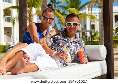 Sexy young couple lounging on an outdoors bed in a tropical hotel. Attractive elegant young couple drinking a cocktail. - stock photo