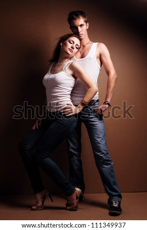 Sexy young couple wearing jeans against in the studio - stock photo