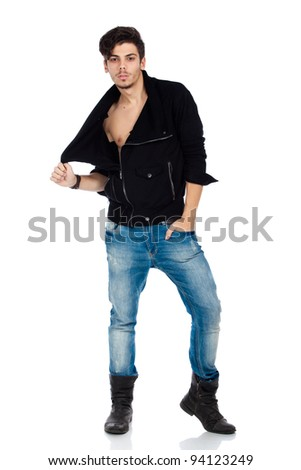 Sexy young fashion model wearing jeans, boots and a black jacket. Isolated on white background. Studio vertical image. - stock photo
