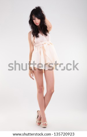 sexy young fashion woman holding her hand behind her head and looking down. on gray background - stock photo