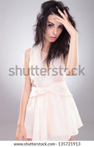 sexy young fashion woman holding her hand in her hair and looking at the camera. on gray background - stock photo