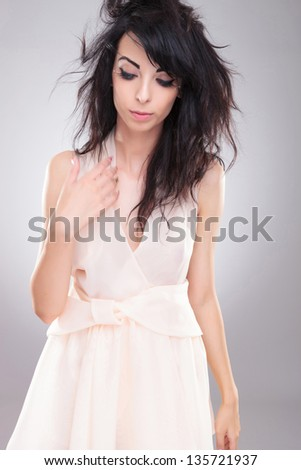 sexy young fashion woman looking down while she throws her hair back. on gray background - stock photo