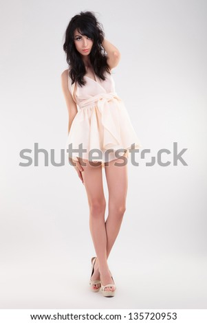 sexy young fashion woman posing with a hand on a thigh and one behind her head wjile looking at the camera. on gray background - stock photo