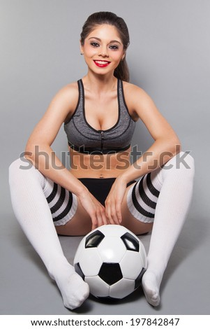 sexy young female in sports outfit holding a soccer ball in studio  - stock photo