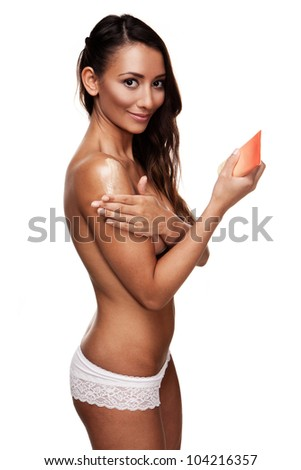 Sexy young female rubbing creme on herself isolated on white - stock photo