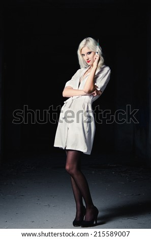 Sexy young girl in the image of nurse with syringe in hand standing among the dark - stock photo