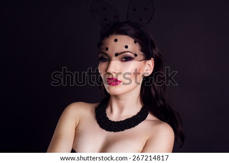 Sexy young girl is wearing bunny lace ears mask with veil and black body isolated on black - stock photo