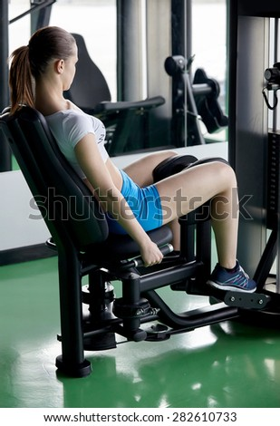 sexy young girl resting after dumbbells exercises. Fitness woman in modern gym. - stock photo