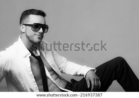 Sexy young male model wearing sunglasses sitting with unbuttoned shirt black and white portrait - stock photo
