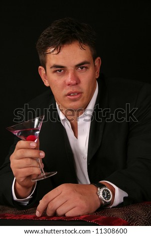 Sexy Young man dressed for a special occasion in a formal tuxedo with cocktail - stock photo