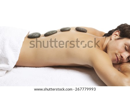 Sexy young man relaxing in spa, lastone therapy - stock photo