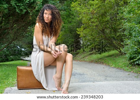 Sexy young multi-ethnic woman in white dress sitting on vintage suitcase next to road - stock photo