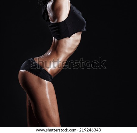 sexy young muscled fitness brunette girl back posing over black background. Fitness woman in sport wear with perfect fitness body  - stock photo