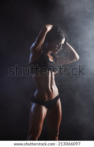 sexy young muscled fitness brunette girl posing over black background. Fitness woman in sport wear with perfect fitness body  - stock photo