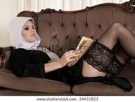 Sexy young nun reading Bible - stock photo