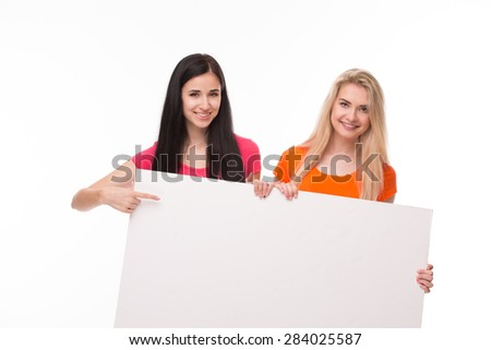 Sexy young pretty girlfriends carrying white poster. Girl standing in pink T-shirt pointing out. - stock photo