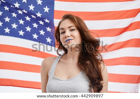 Sexy young white brunette girl celebrating National Independence Day on 4th of July in United States of America with painted face. Attractive model with toothy smile, flag on the background - stock photo