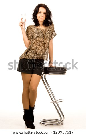 Sexy young woman in a trendy miniskirt enjoying a drink as she leans on a modern design stool isolated on white - stock photo