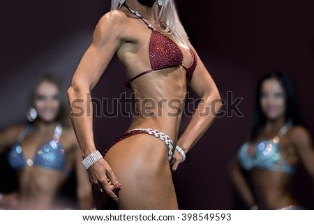 Sexy young woman in bikini. Fitness bikini athlete on stage. Sport gives way to success. Perfect proportions of female body. - stock photo