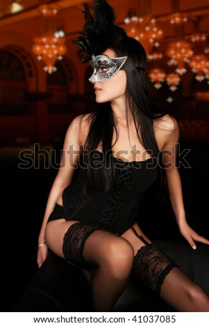 Sexy young woman in lingerie and mask in classic ballroom - stock photo