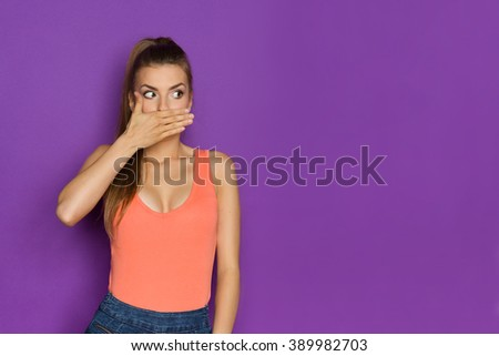 Sexy young woman in orange shirt cover her lips and looking away at copy space.Waist up studio shot on purple background. - stock photo