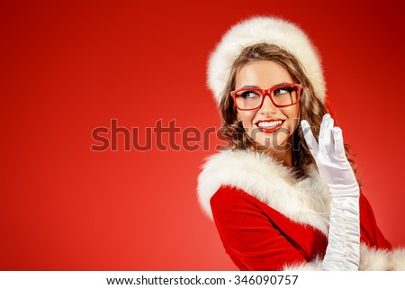Sexy young woman in Santa Claus clothes and elegant red glasses. Red background. Christmas celebration. - stock photo