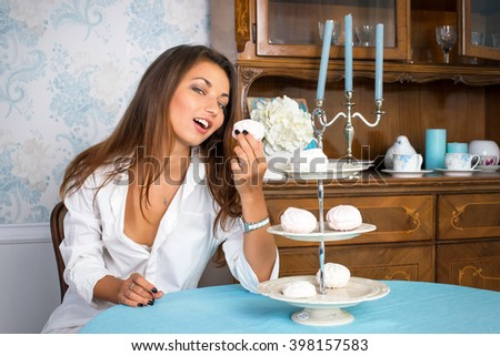 Sexy young woman in white man's shirt eating sweets in luxury light interior - stock photo