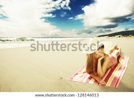 Sexy young woman lying down on the beach - stock photo