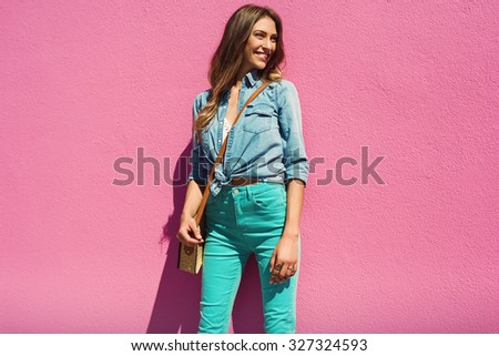 Sexy young woman on pink wall in jeans shirt and mint pants. Fashion photo - stock photo