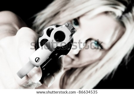 Sexy young woman pointing a gun Focus is on Gun - stock photo