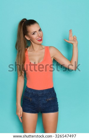Sexy young woman posing and showing finger gun. Three quarter length studio shot on teal background. - stock photo
