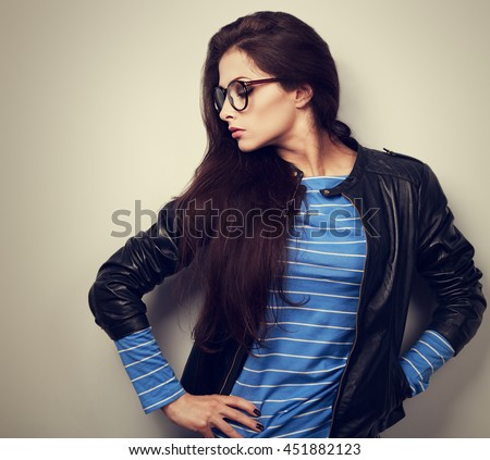 Sexy young woman posing in fashion black leather jacket and glasses. toned vintage closeup portrait - stock photo