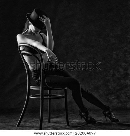 Sexy young woman sitting on a chair on a black background. - stock photo