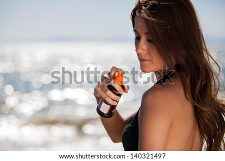 Sexy young woman spraying some tanning lotion on her shoulder on a sunny day - stock photo