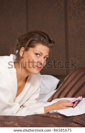 Sexy young woman texting while lying on a bed at home - stock photo