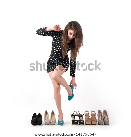 Sexy young woman trying different kinds of shoes on white background. - stock photo