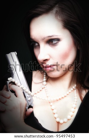 Sexy young woman with a gun, pearl on green background - stock photo