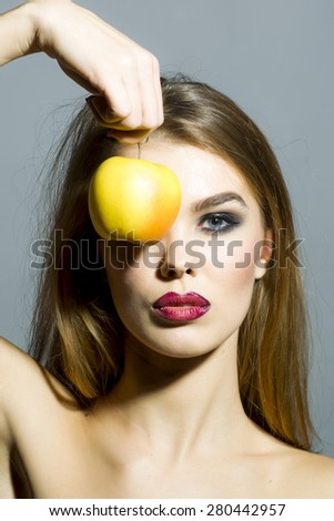 Sexy young woman with bright make up looking forward holding fresh yellow apple covering eye standing on gray background copyspace, vertical picture - stock photo