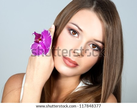 Sexy young woman with flowers - Beautiful portrait of a sexy woman with bright pink orchid - stock photo