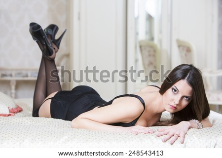 Sexy young woman with long dark hair in black lingerie lying down in the bed. - stock photo