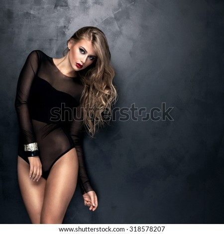 Sexy young woman with long hair posing in black lingerie, standing, looking at camera. Studio shot. Girl with glamour makeup.  - stock photo