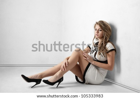 Sexy young woman with long legs sitting on floor near room wall - stock photo