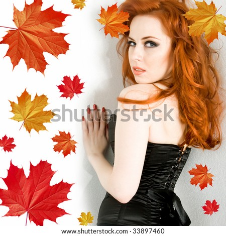 Sexy young woman with red hair and maple leaves - stock photo