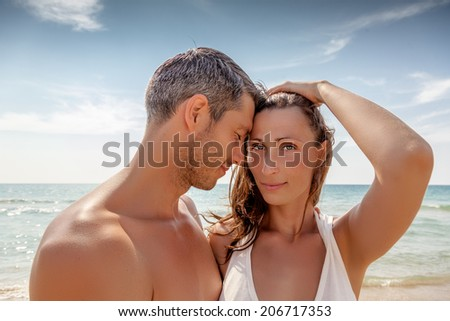 sexy younger parents couple on the beach  - stock photo