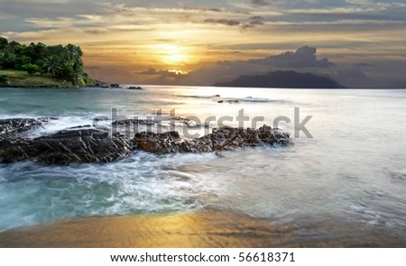 Seychelles Long Exposure for soft water effect looking out to Silhouette island at Sunset - stock photo
