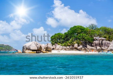 Seychelles, motor boat against the tropical backdrop of the rocky island. People bathe. Sunny day. - stock photo