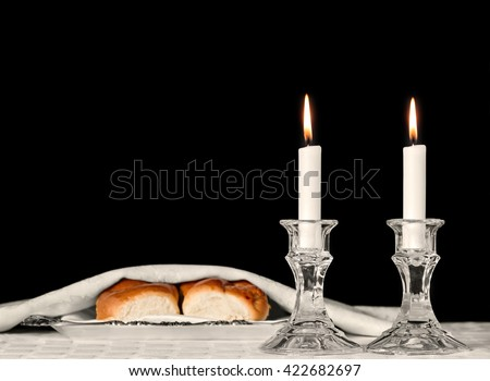 Shabbat candles in glass candlesticks isolated on black. Blurred background of covered challah bread in silver tray on white tablecloth. Copyspace.  - stock photo