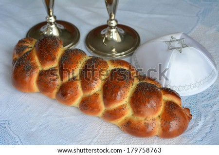 Shabbat eve table with uncovered challah bread, candles and kippah. - stock photo