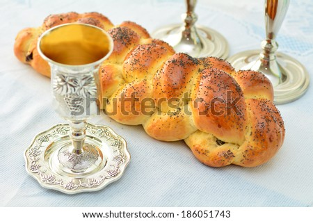 Shabbat eve table with uncovered challah bread, Sabbath candles and Kiddush wine cup. - stock photo