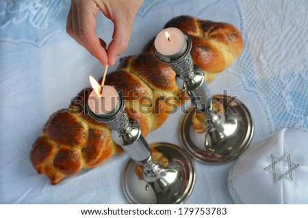 Shabbat eve table.Woman hand lit Shabbath candles with uncovered challah bread and kippah. - stock photo